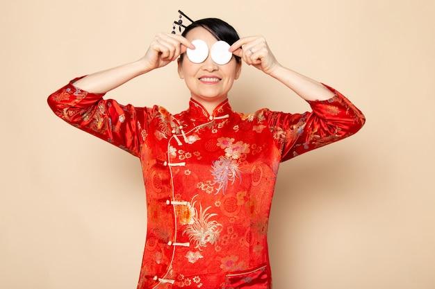 Вид спереди красивая японская гейша в традиционном красном японском платье с волосяными палочками позирует, держа маленький белый хлопок, элегантно улыбаясь на кремовом фоне церемонии японии