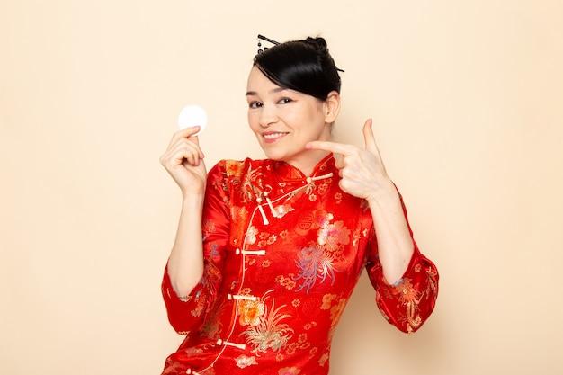 クリーム色の背景に笑みを浮かべて小さな白い綿を浮かべてポーズをとってポーズをとって髪棒で伝統的な赤い和服で正面日本の美しい芸者