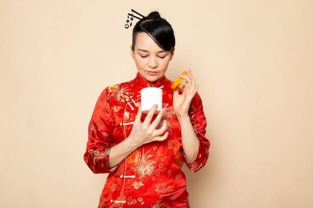 Вид спереди красивая японская гейша в традиционном красном японском платье с заколками для волос позирует, открывая кремовую банку на кремовом фоне, церемония япония