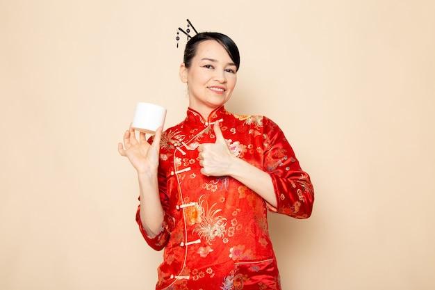 Вид спереди красивая японская гейша в традиционном красном японском платье с заколками для волос позирует в кремовой банке на кремовой фоновой церемонии япония