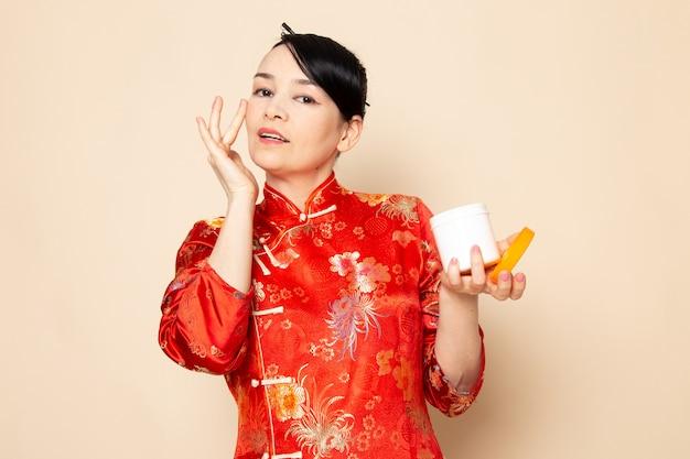 クリーム色を使用してポーズをとって髪棒でポーズをとって伝統的な赤い和服の正面日本の美しい芸者