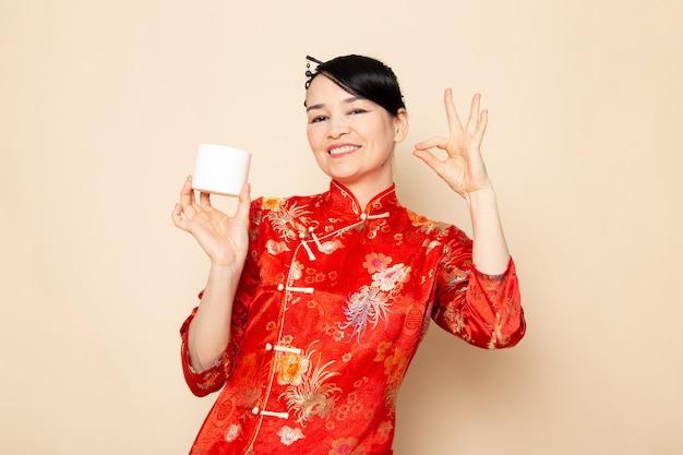 Вид спереди красивая японская гейша в традиционном красном японском платье с заколками для волос позирует в кремовой банке улыбается на кремовом фоне церемонии японии