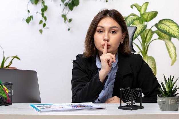 Вид спереди красивая молодая деловая женщина в черной куртке и синей рубашке, показывающая знак молчания перед столом бизнес-офис работы