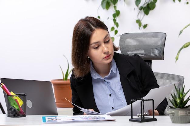 Вид спереди красивая молодая деловая женщина в черной куртке и синей рубашке, работающая с ноутбуком и документами перед рабочим столом бизнес-офиса
