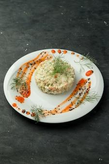 Салат оливье на тарелке, украшенный соусом и укропом