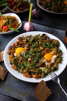 Вид спереди черные баклажаны, нарезанные вместе с нарезанными овощами, зелеными листьями внутри белой тарелки и чипсами на сером столе, витаминные овощи