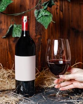Вид спереди бутылка вина красного вина с бордовым колпачком, а также стеклянные и зеленые листья на фоне алкогольной винодельни