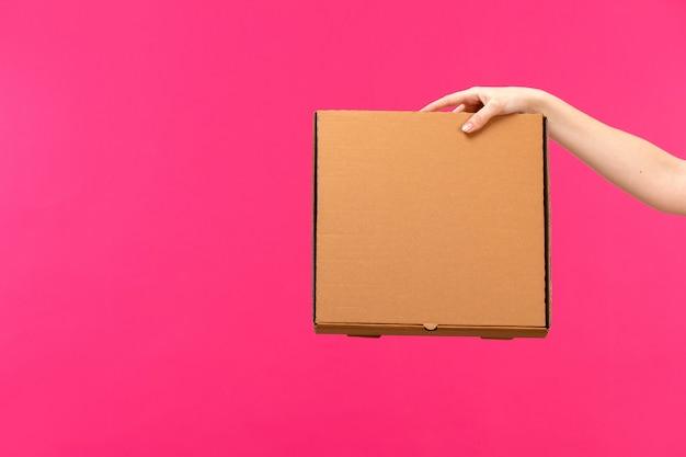 茶色の箱の女性の手ピンクの背景色の食品パッケージを持っている正面の茶色のボックスの手