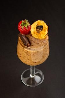 正面図茶色のチョコデザートおいしいおいしい甘い粉コーヒーチョコバーと暗い背景に新鮮なイチゴの甘いさわやかなデザート
