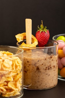正面図茶色のチョコデザートおいしいコーヒーと粉末コーヒーチョコバーとストロベリーコーンフレークとキャンディーと暗い背景の甘いさわやかなデザート