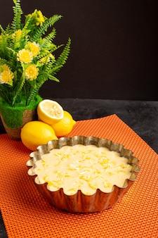 暗い机の上に正面を描いたおいしいレモンケーキの酸っぱいエキゾチックなベーカリーケーキの甘い