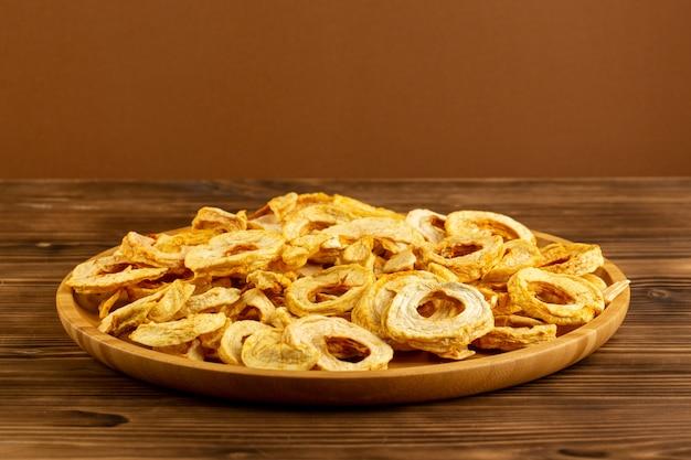 Вид спереди сушеные ананасовые кольца внутри коричневого стола кисло-сладкий вкус на коричневом фоне фрукты сухой продукт