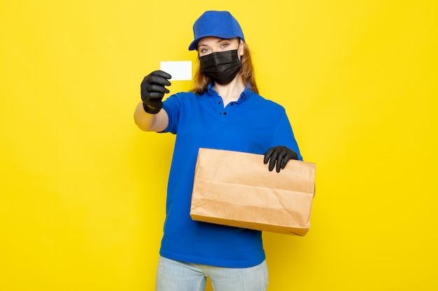 Фронтальный вид женского привлекательного курьера в синей рубашке поло, синей кепке и джинсах в черных перчатках, черной защитной маске, держащей пакет на желтом фоне, в службе общественного питания