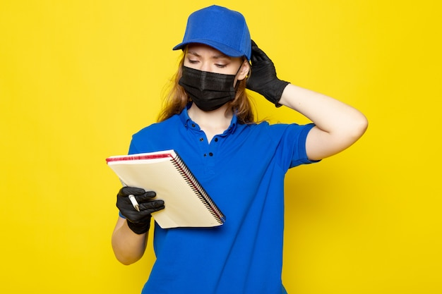 青いポロシャツの青い帽子のジーンズと黒の手袋のジーンズの正面図女性魅力的な宅配便黄色の背景のフードサービスの仕事にペンとノートを保持