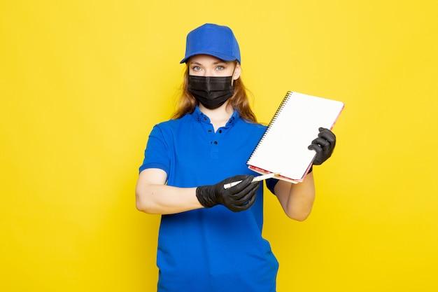 Фронтальный вид женского привлекательного курьера в синей рубашке поло, синей кепке и джинсах в черных перчатках, черной защитной маске на желтом фоне работы общественного питания