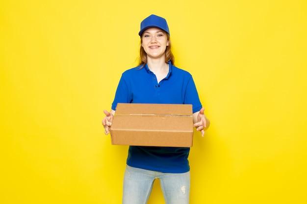 青いポロシャツブルーキャップとジーンズの黄色の背景のフードサービスの仕事に保持パッケージを笑顔で正面の女性の魅力的な宅配便
