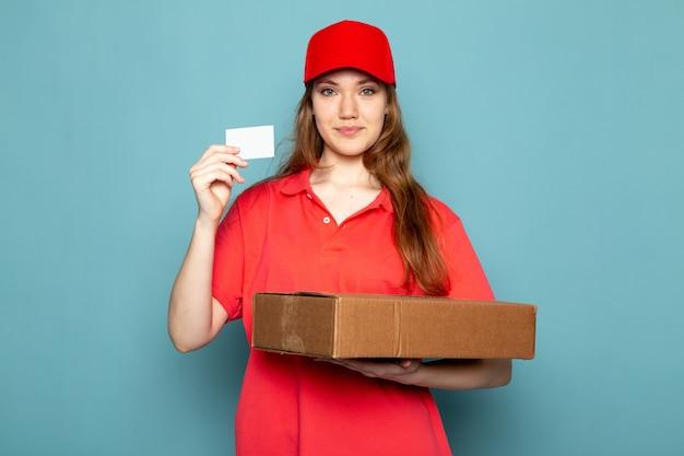 Вид спереди женщина привлекательный курьер в красной рубашке поло, красной кепке и джинсах, держа коробку позирует, улыбаясь на синем фоне работы общественного питания
