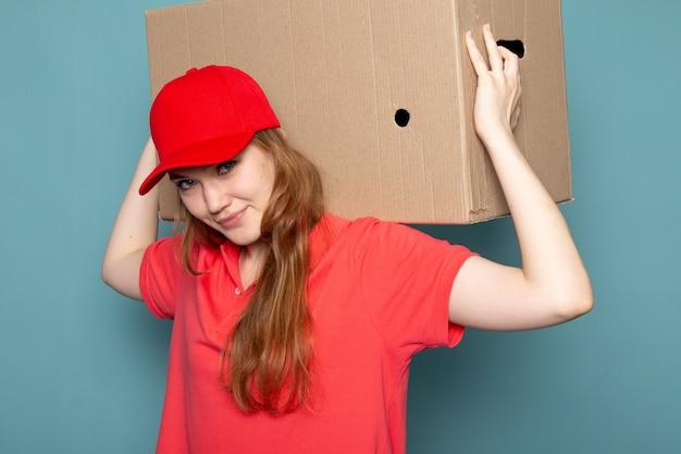 赤いポロシャツの赤い帽子とジーンズの青い背景のフードサービスの仕事でポーズパッケージボックスを保持している正面の女性の魅力的な宅配便