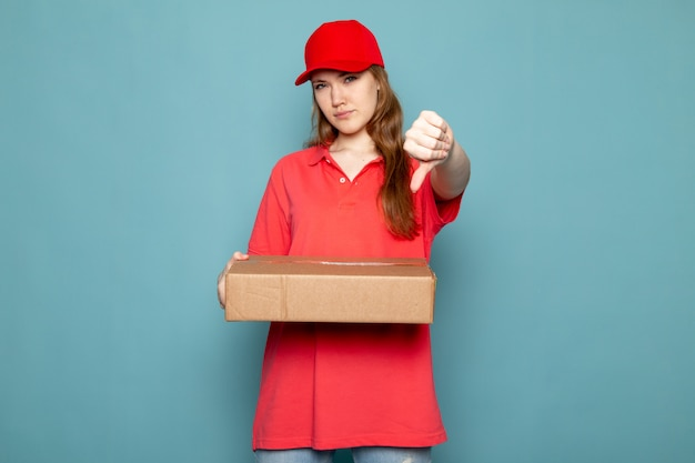 赤いポロシャツの赤い帽子とジーンズが青い背景のフードサービスの仕事に大きな兆候を示さないポーズをとって保持している正面の女性の魅力的な宅配便