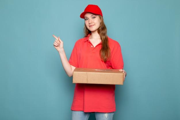 Вид спереди женщина привлекательный курьер в красной рубашке поло, красной кепке и джинсах держит пакет позирует улыбается на синем фоне работа общественного питания