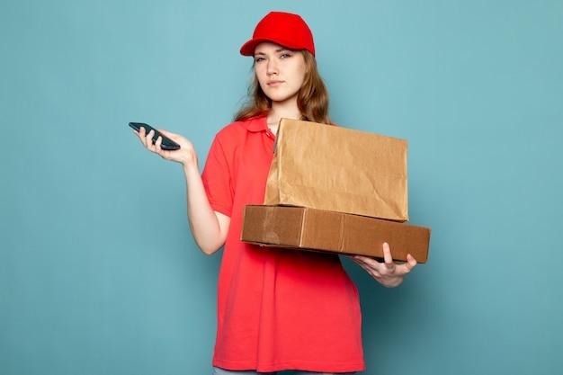 青い背景のフードサービスの仕事で彼女の電話を使用して茶色のパッケージを保持している赤いポロシャツの赤い帽子の正面の女性の魅力的な宅配便