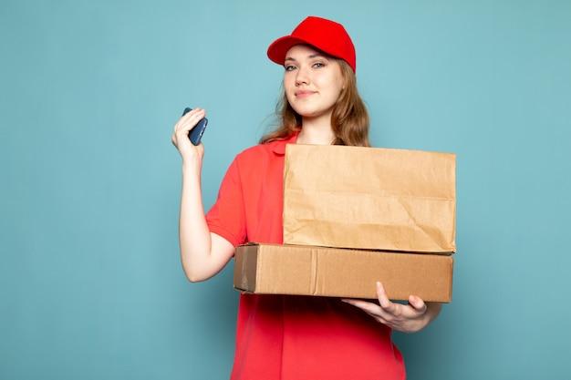Вид спереди женщина привлекательный курьер в красной рубашке поло, красной кепке, держа коричневый пакет, используя ее телефон, улыбаясь на синем фоне работы общественного питания