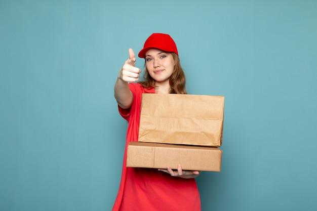 Вид спереди женщина привлекательный курьер в красной рубашке поло, красной кепке, держа коричневые пакеты, улыбаясь позирует на синем фоне работы общественного питания