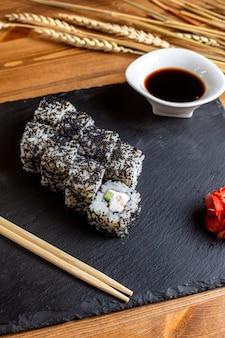 Рыбные рулеты с видом спереди, заполненные нарезанными овощами рисом и рыбой из черного соуса