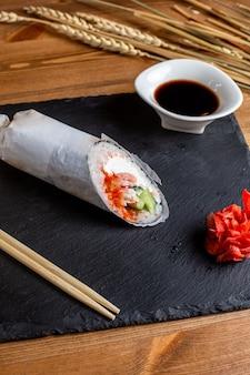 正面玄関の魚ロールと野菜のスライスご飯、ブラックソースの食事魚日本