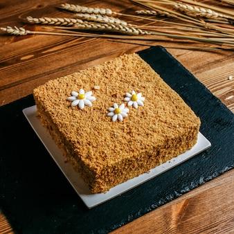 カモミールスクエアで飾られた正面図の蜂蜜ケーキは、茶色の背景に白いプレート菓子の甘さの誕生日の中においしい誕生日ケーキを形成しました