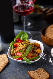 Картофель спереди, нарезанный вместе с нарезанными овощами, зелеными листьями на белой тарелке и чипсами красного вина на серых столах с витаминными овощами