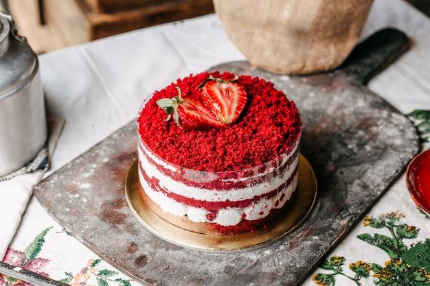 茶色の机の上のクリームのおいしい甘い誕生日のお祝いで丸いイチゴで飾られた正面の赤いフルーツケーキ