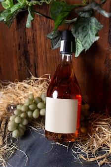 Бутылка виски, вид спереди, зеленый виноград и зеленые листья, изолированные на коричневом фоне.