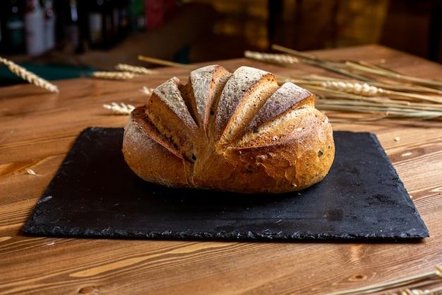 正面の白パン、焼きたてのベーカリー、食欲をそそる黒い組織のペストリー生地のおいしい食欲