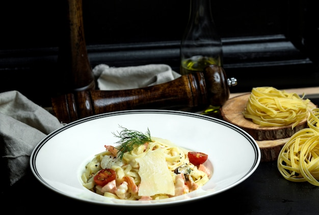 クリーミーなソースのシーフードフェットチーニ、チェリートマトとディルをトッピングしたパルメザンチーズ