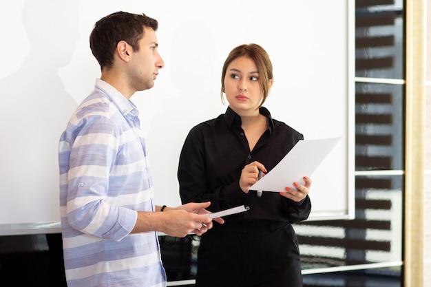 若い女性が机の上のグラフィックについて議論する若い男と一緒に黒いシャツを着た正面の若い魅力的な実業家