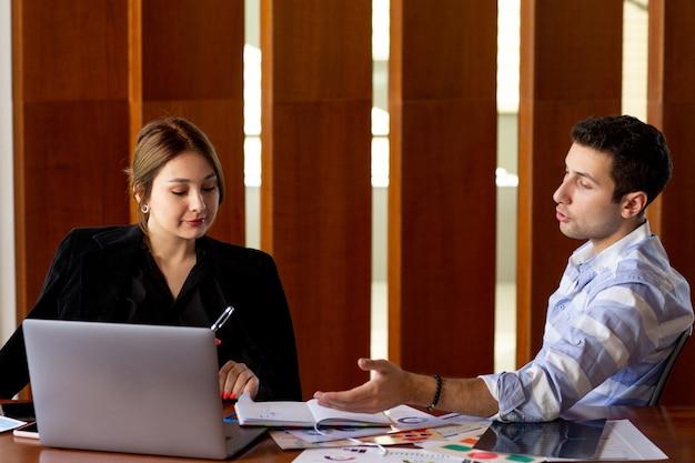 若い男と一緒に黒いシャツの黒いジャケットの正面の若い魅力的な女性実業家と彼女のオフィスの仕事の建物の中で仕事の問題を議論します。