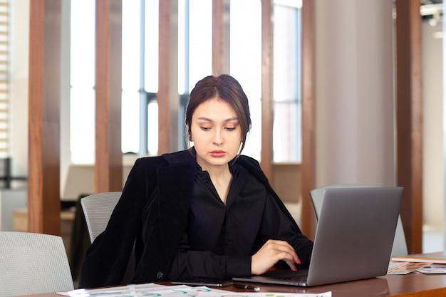 Вид спереди молодой привлекательной бизнес-леди в черной рубашке черный пиджак, используя свой серебряный ноутбук, работающих внутри ее офисной работы