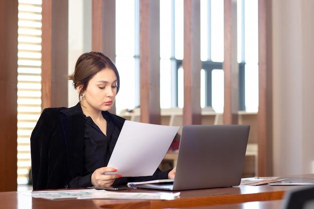 Вид спереди молодой привлекательной бизнес-леди в черной рубашке черный пиджак, используя ее серебристый ноутбук, написание чтения, работающих в ее офисе работа работа здания