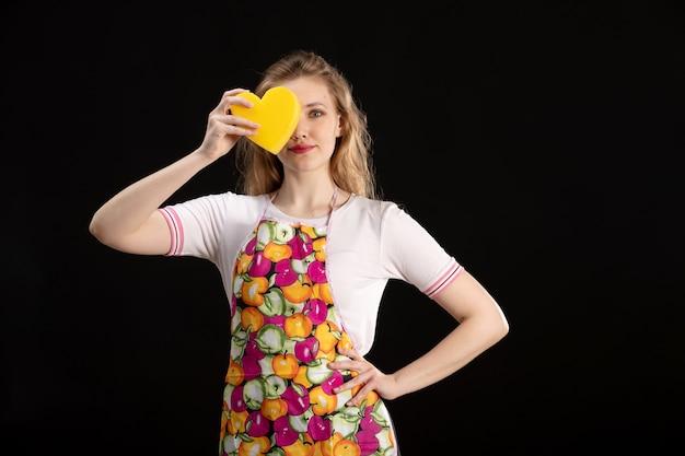 黒い背景に黄色のハートの形を保持している笑顔のカラフルなケープの正面の若い魅力的な女の子愛笑顔陽性