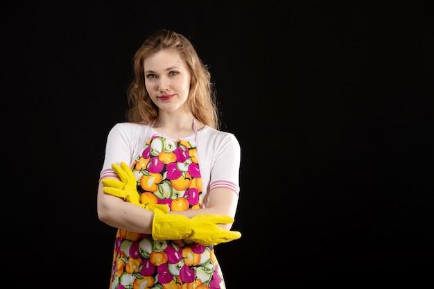 笑顔のカラフルな岬の正面の若い魅力的な女の子笑顔黄色の手袋を身に着けている黒の背景に幸せなエキサイティングな愛笑顔陽性