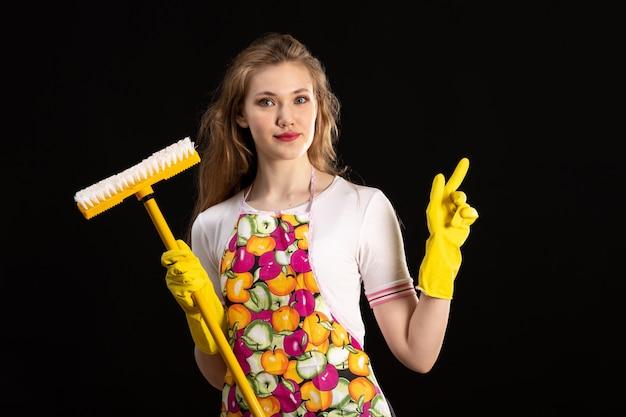黒の背景に黄色のモップを保持している黄色の手袋を身に着けている笑顔のカラフルなケープの正面の若い魅力的な女の子愛笑顔陽性