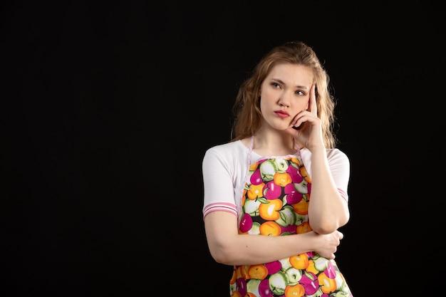 黒の背景の主婦の掃除を考えてカラフルなケープの正面の魅力的な少女
