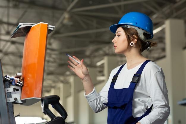 Вид спереди молодая привлекательная дама в синем строительном костюме и шлем управления машинами в ангаре во время дневного строительства зданий архитектуры