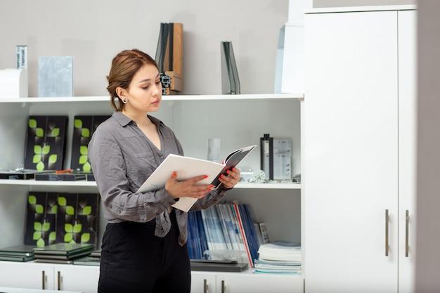 Вид спереди молодая привлекательная дама в серой рубашке и черных брюках просматривает книги и журналы возле стойки с книжной комнатой