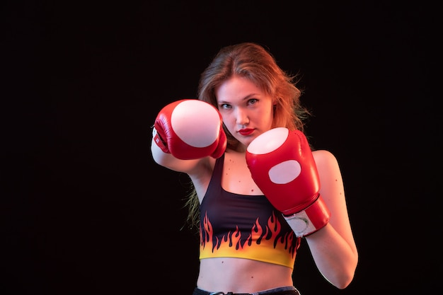 赤いボクシンググローブの正面若い魅力的な女性は黒の背景のスポーツボクシングトレーニングにシャツを火します。