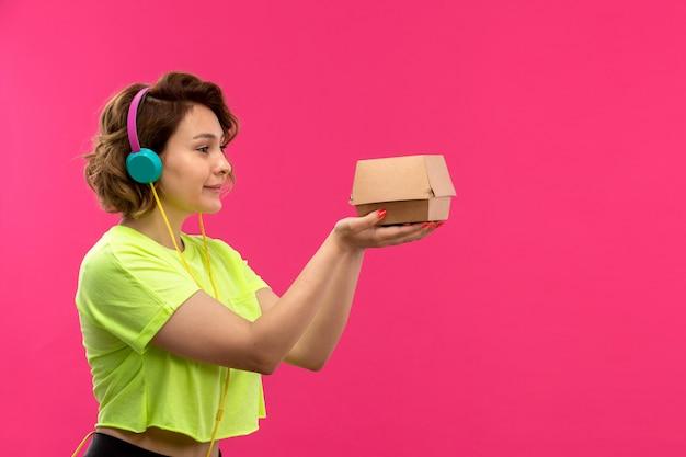 ピンクの背景の若い女性の音楽に茶色のボックスを保持している酸性色のシャツ黒ズボンの正面の若い魅力的な女性