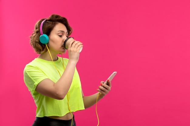 Вид спереди молодой привлекательной женщины в кислотной рубашке, черных брюках в синих наушниках, слушающих музыку с помощью телефона, пьющих кофе на розовом фоне молодой женской молодежи