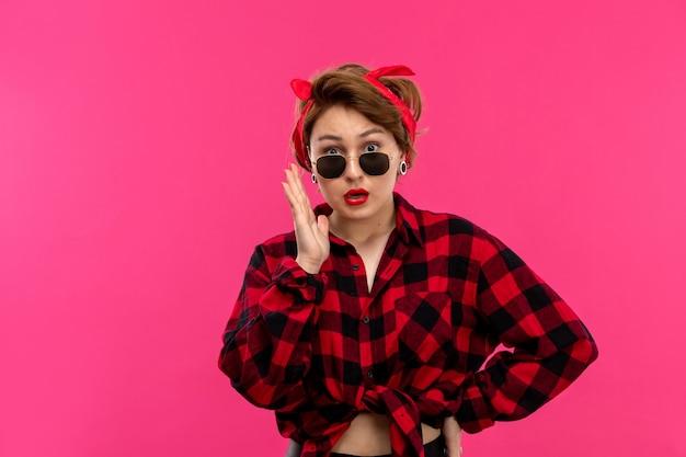 ピンクの背景の若い女性のファッションでポーズのサングラスでショックを受けた市松模様の赤黒シャツ黒ズボンで正面の若い魅力的な女性
