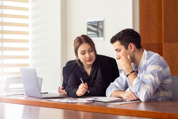若い男と一緒に彼女のオフィス仕事の仕事の建物内の仕事の問題を議論する黒いシャツの黒いジャケットの正面の若い美しい女性実業家